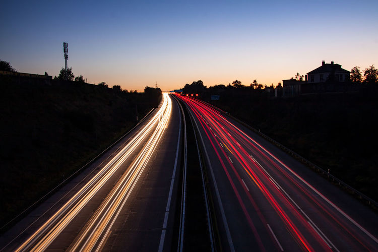 High angle view of light trails on highway at dusk