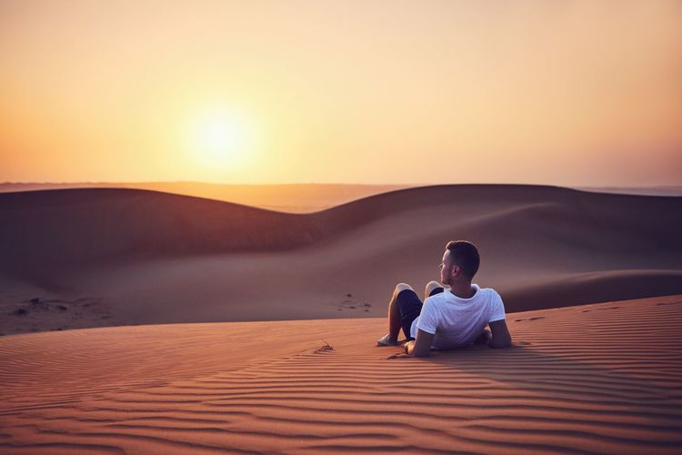 Idyllic sunrise in desert. Young man contemplation on sand dune. Wahiba Sands in Oman. Man Lying Down Relaxation Resting Contemplation Thinking Vacations Adventure Freedom Carefree Rear View Young Men Looking At View Sun Sunrise Sand Dune Desert Oman Travel Destinations Travel Sunset Sand Tranquility Landscape Nature