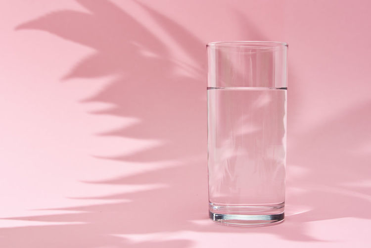 Glass of water and leaf shadow on pink background