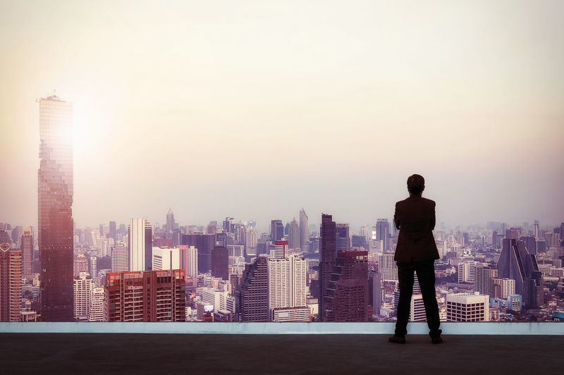 Vision concept. Successful businessman standing with hands crossed on chest, On top of building and looking through Cityscape Skyline Night Light. Top Building Businessman City Looking Man Roof Business Standing Skyscraper Modern View Success Office People Male Suit person Sky Concept Creative Manager Boss New Rooftop Vision Background Urban Day Cityscape Mission Skyline Perspective Night Up Future Professional Good Glasses Human Executive  Leadership Outdoor Think Leader