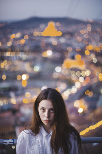 Portrait of young woman standing against defocused lights at night