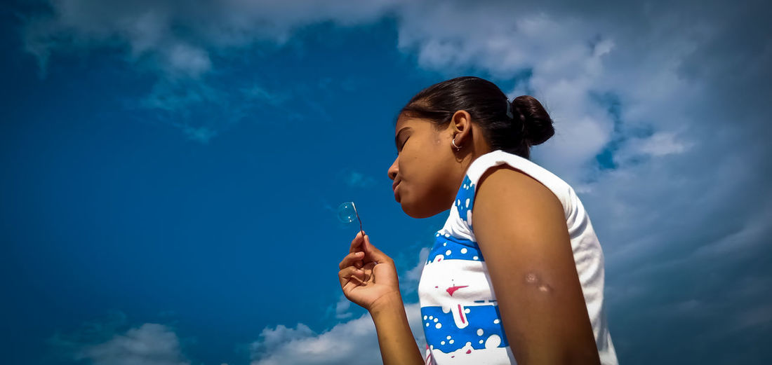 Low angle view of a girl standing against blue sky