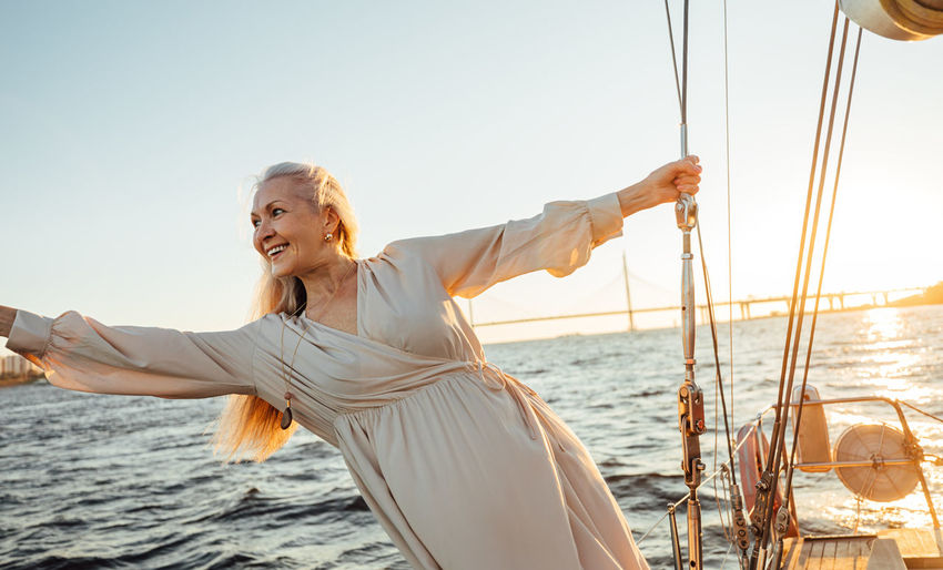 Smiling senior woman on sailboat in sea against sky
