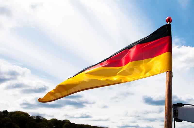 German Flag Waving Against Cloudy Sky