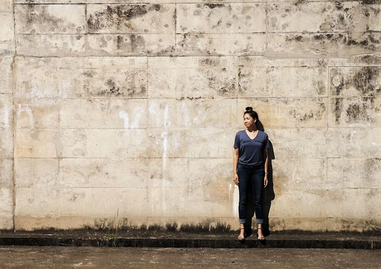 Full length of woman standing on footpath against wall