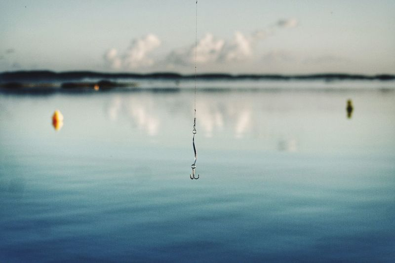 Close-up of water drop on lake against sky