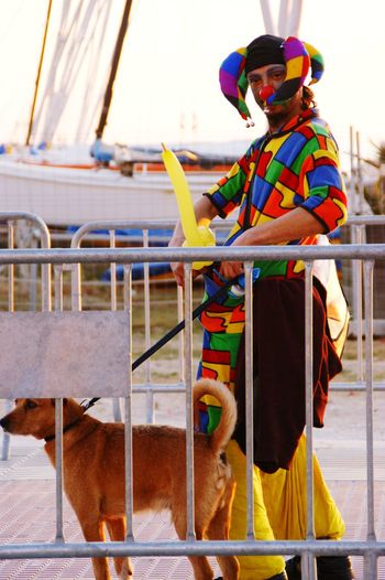 Side view of man in clown costume with dog