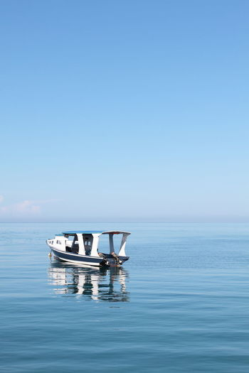 An empty motor boat in sulawesi sea against clear sky