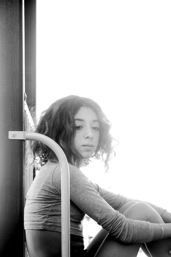 Portrait of girl sitting at doorway