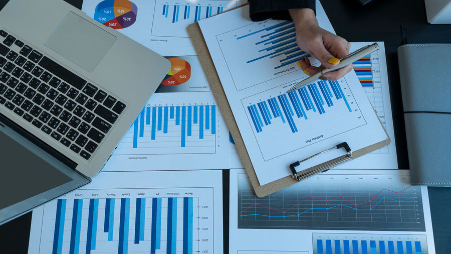 Cropped hand of businesswoman holding pen over graph and charts