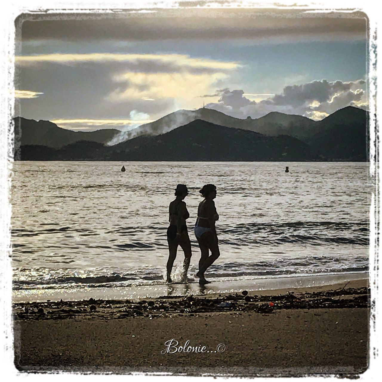 mountain, two people, water, togetherness, real people, full length, nature, scenics, beach, sky, silhouette, bonding, beauty in nature, sea, men, lifestyles, cloud - sky, mountain range, vacations, leisure activity, sand, outdoors, day, people