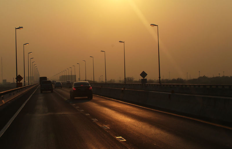 Cars on highway against sky during sunset