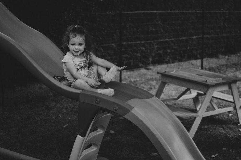 Full length of happy girl enjoying slide at playground