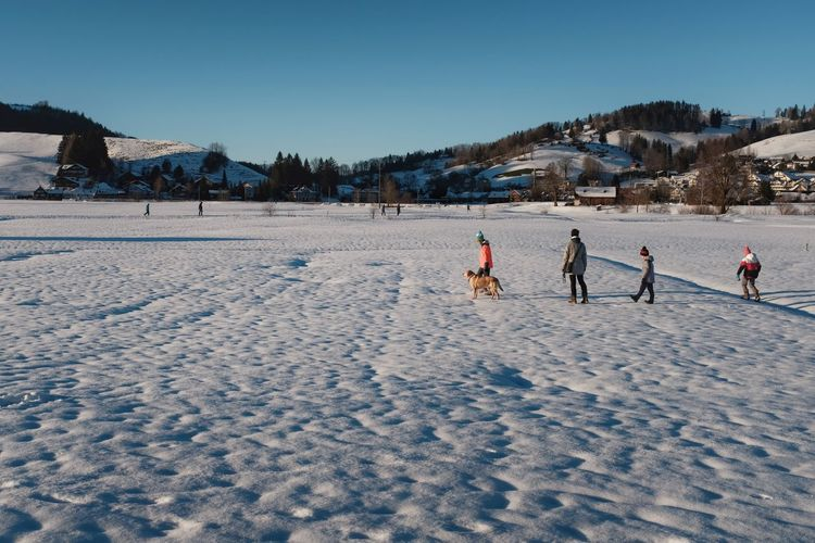 People playing on snow covered land against sky