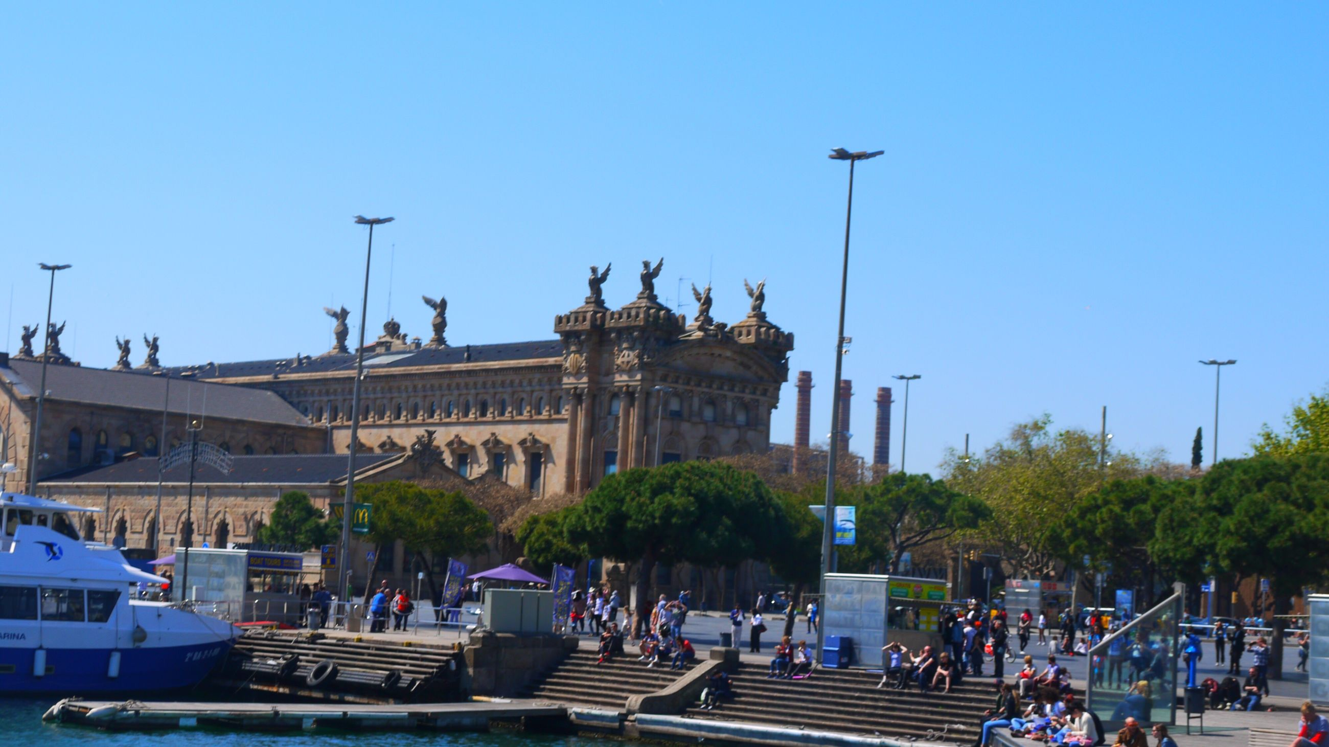clear sky, city, building exterior, outdoors, architecture, statue, fountain, sculpture, large group of people, day, sky, people