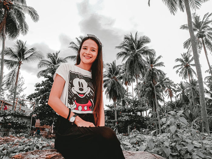 Portrait of smiling young woman standing on palm trees