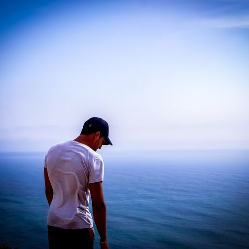 Man looking at sea against sky
