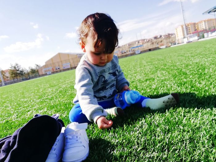 Cute Baby Boy Sitting On Grassy Field During Sunny Day
