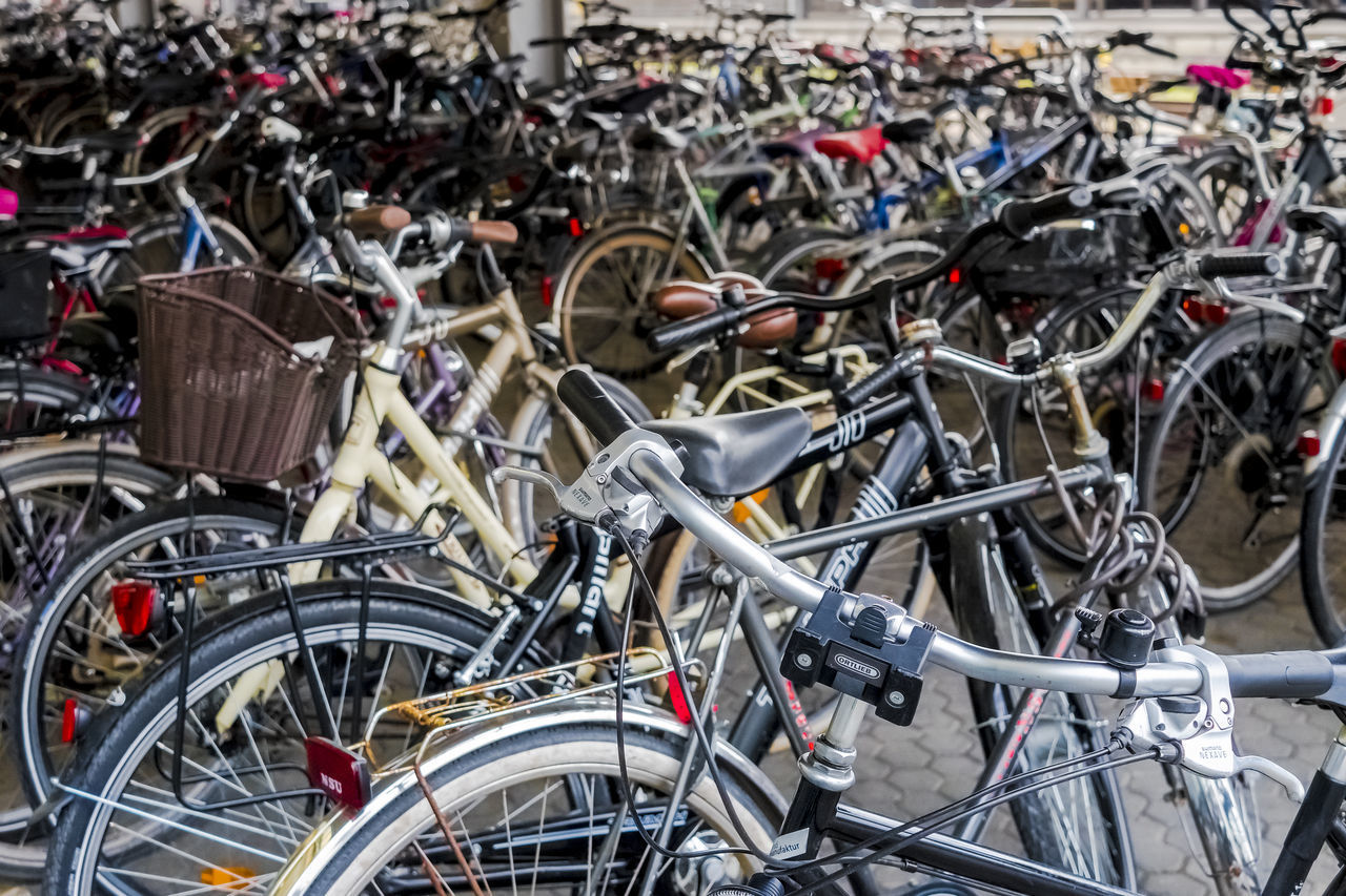 bicycle, transportation, mode of transportation, land vehicle, stationary, large group of objects, no people, day, focus on foreground, outdoors, parking lot, abundance, metal, city, group, in a row, wheel, street, nature, security, spoke, junkyard