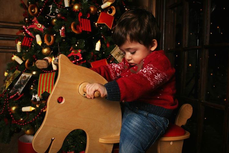 Boy Riding On Rocking Horse By Christmas Tree At Home