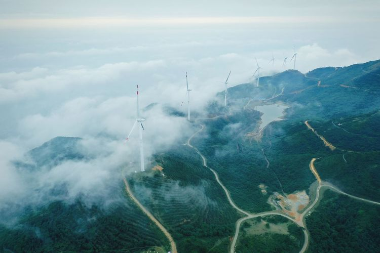 Aerial view of windmills on landscape against sky