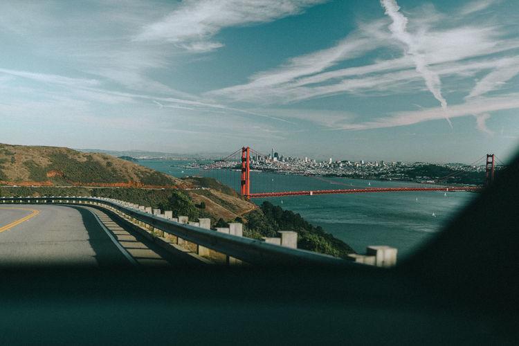 Road by golden gate bridge over bay against sky