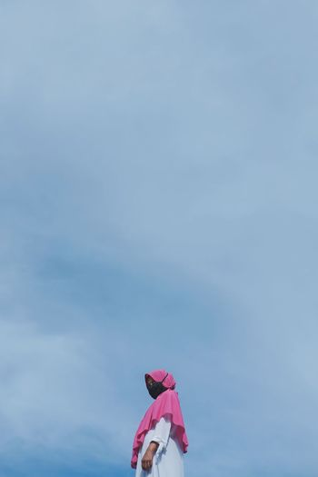 Low angle view of pink umbrella against blue sky