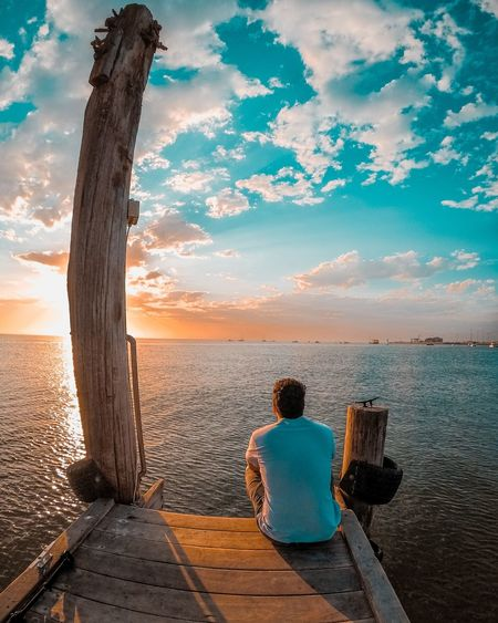 Rear view of man sitting by sea against sky