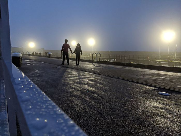 Rear view of silhouette couple standing on bridge at night