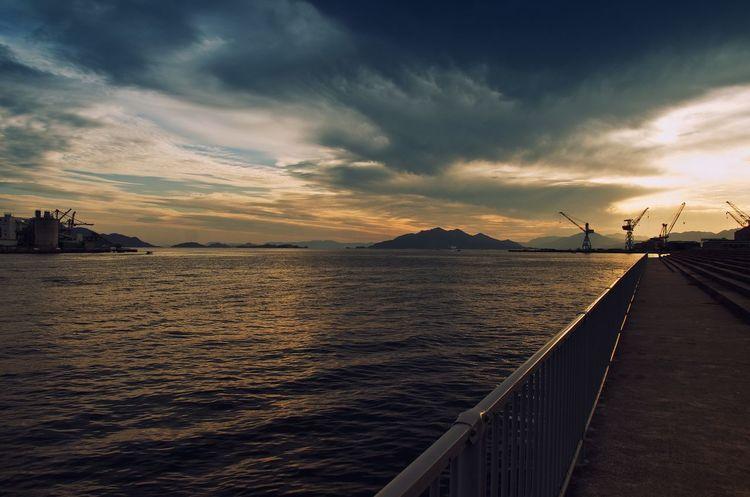 Ujina, Japan Sunset Sundown Dusk Landscape Seascape Clouds Harbour Port Skyline Coast Coastline Waves Water Sea Ocean Reflection Golden Japan Railing Slihouettes Mountains Cranes