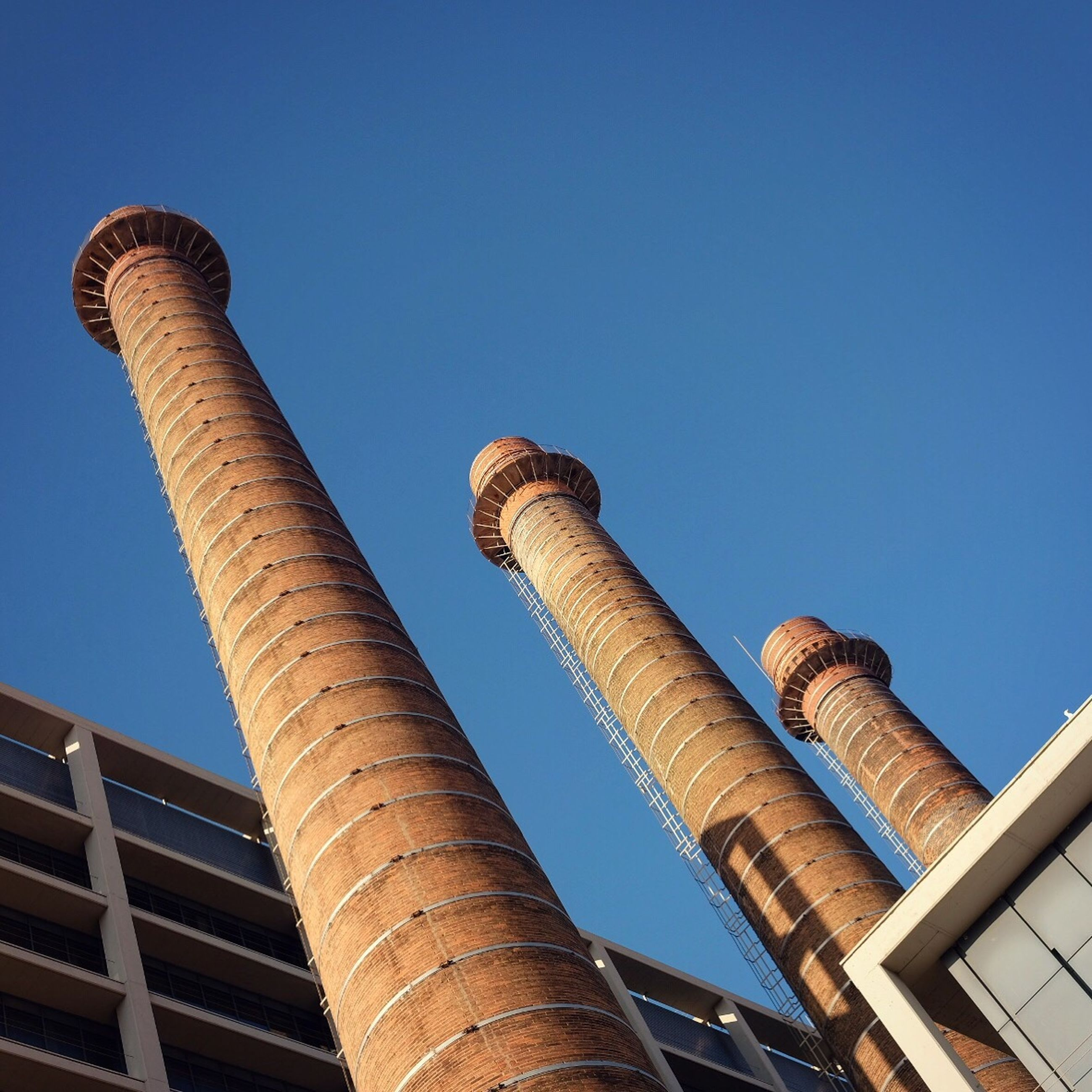 low angle view, clear sky, architecture, building exterior, blue, built structure, tall - high, city, no people, tower, industry, outdoors, sky, factory, smoke stack, day, skyscraper
