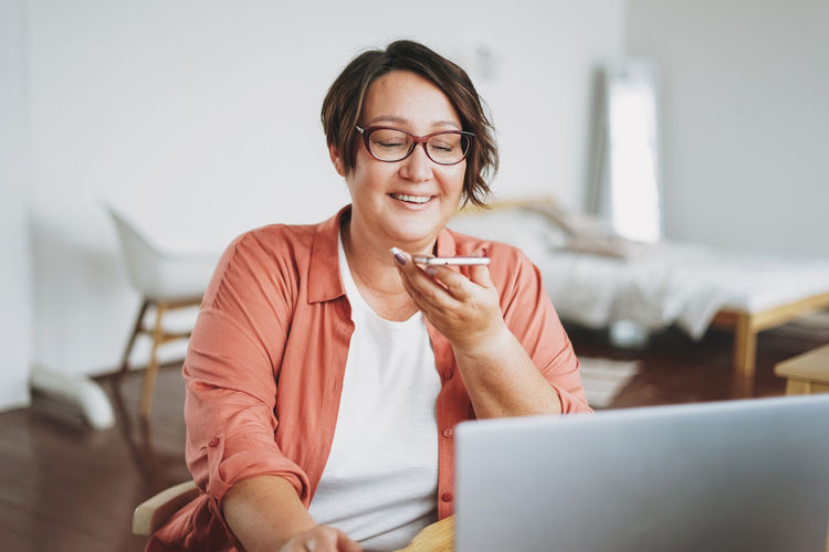 Adult charming brunette woman in glasses plus size body positive working with laptop at home
