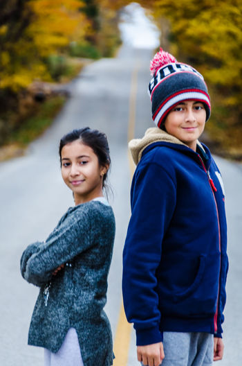 Portrait of smiling siblings standing on road during autumn