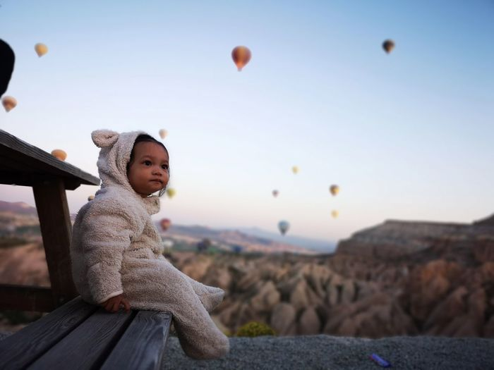 Baby girl sitting on bench against hot air balloons flying over mountains
