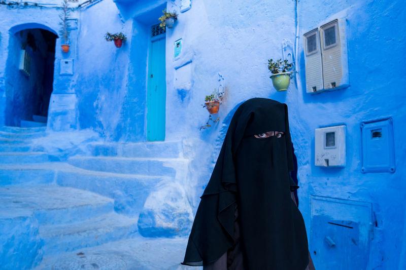 Portrait of woman wearing burka standing against building