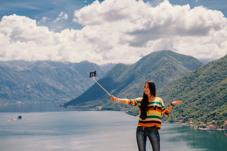 Woman taking selfie while standing at lake against mountains