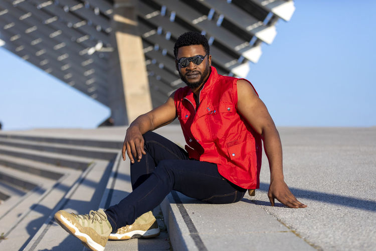 Front view of a young black man wearing sunglasses sitting on staircase in a sunny day while looking camera Glasses One Person Young Men Real People Front View Sitting Men Day Focus On Foreground Architecture Lifestyles Full Length Portrait Casual Clothing Young Adult Looking At Camera Fashion Sunlight Sunglasses Outdoors African American Looking At Camera Sleeveless  Sitting Staircase Stairs Sunlight Daylight Muscular Build Wellbeing