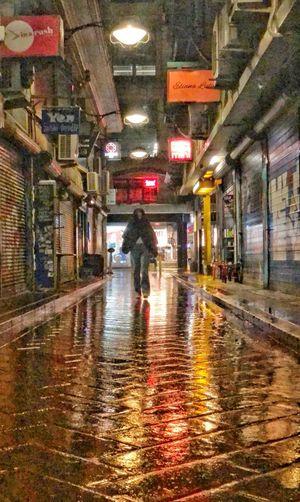 Rear view of wet walking on illuminated road during rainy season