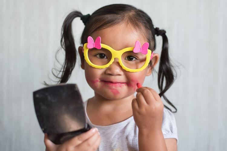 Portrait of smiling girl holding camera
