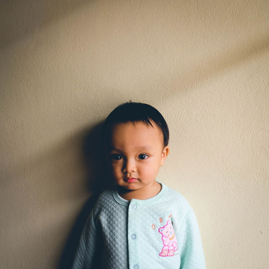 Close-up portrait of baby boy standing by beige wall