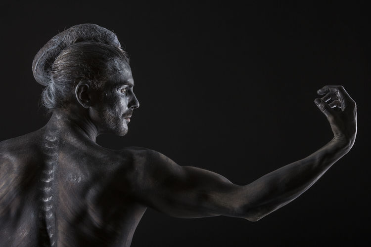 Shirtless muscular man with body paint against black background
