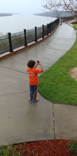 Rear view of boy standing by water
