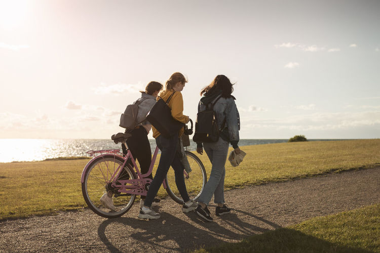 People riding bicycle on shore against sky