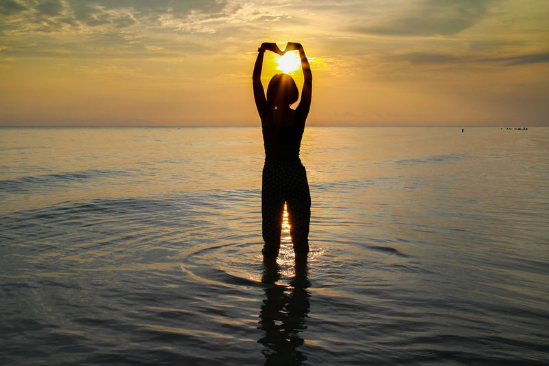 Silhouette woman making heart shape while standing in sea against orange sky