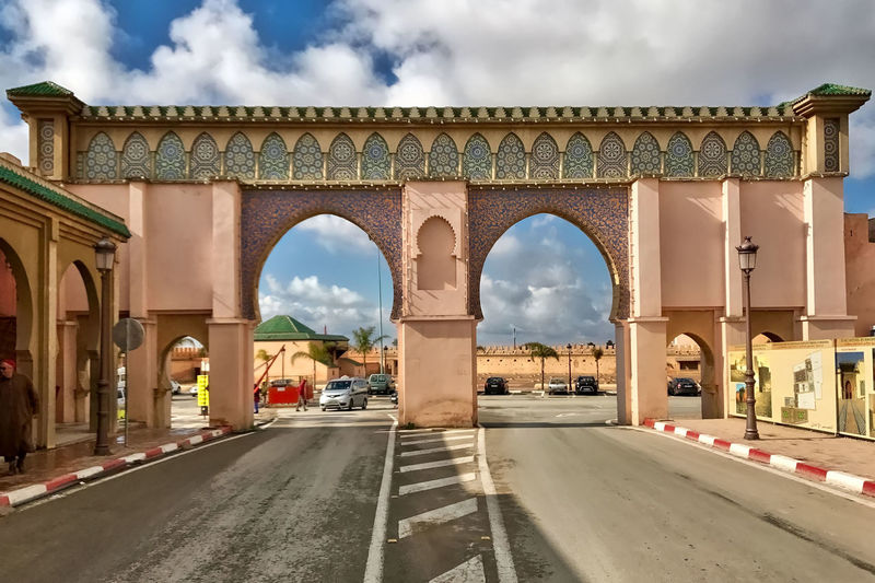 A gate to the Royal Palace at Meknès in Marocco. Arches Cars Clouds Gate Meknès Morocco Ornaments Royal Palace Sky Street