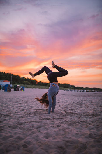 Young woman doing handstand at beach during sunrise