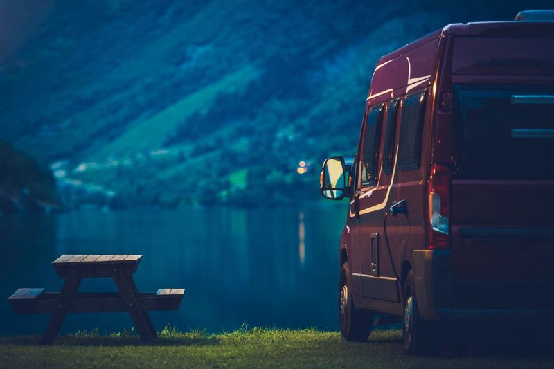 Vehicle And Picnic Table By Lake During Dusk
