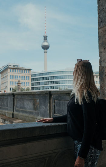 Rear view of woman against buildings in city