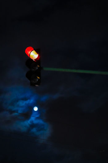 Low angle view of illuminated railway signal against sky at night