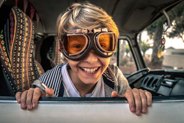 Portrait of happy boy wearing eyewear in car